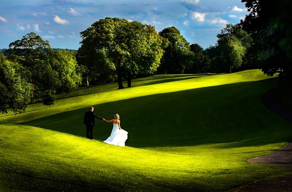 Picture of a bride and groom holding hands and looking across a beautiful green golf course by Stuart Wood Wedding Photography