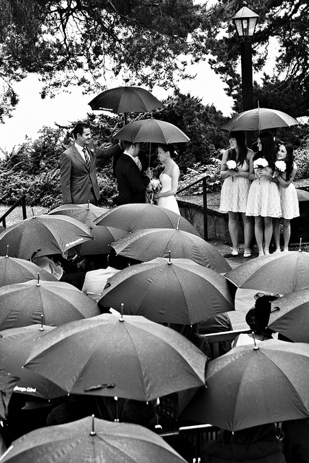 Picture of a wedding ceremony in the rain with umbrellas by Ian Johnson Photography