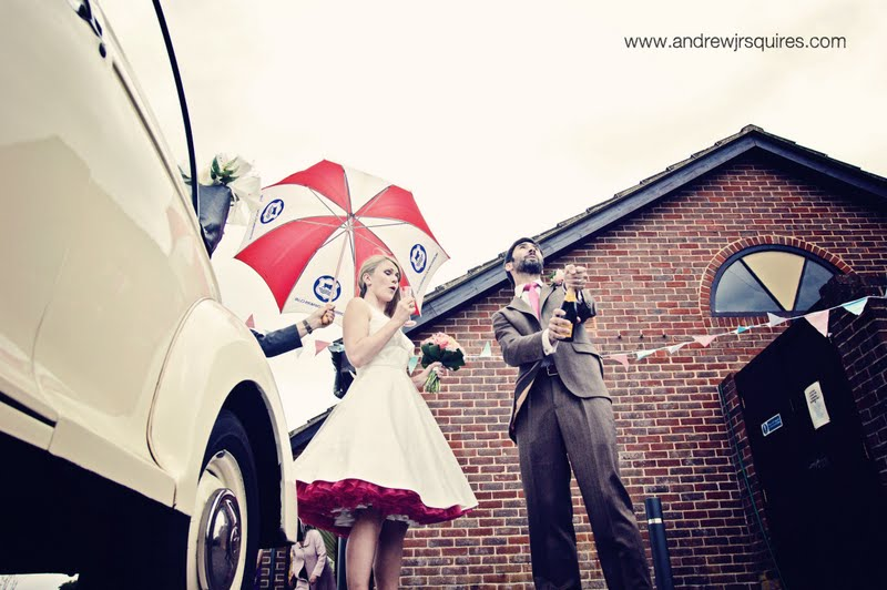 Bride and groom opening a bottle of Champagne by Andrew J R Squires Photography
