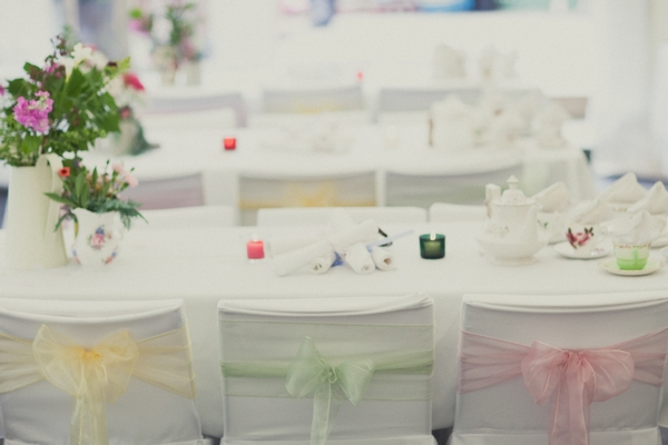 Chair covers with yellow, green and pink sashes by Ambience Venue Styling Bristol