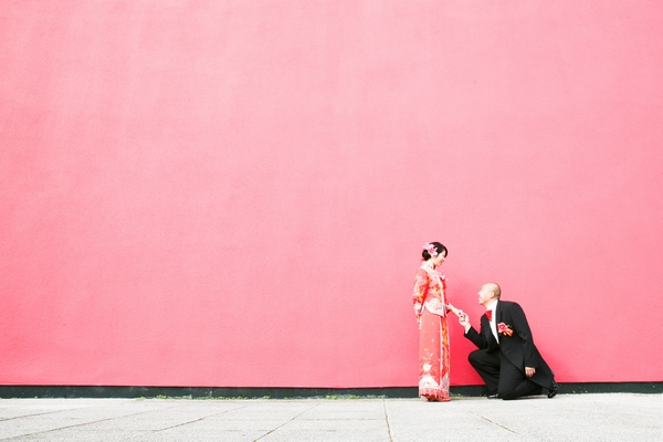 Groom on one knee with his bride in front of a pink wall - Picture by Juliet Lemon Photography
