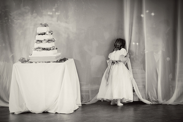 Wedding cake and flower girl peeking through curtain - Picture by Martin Hambleton Photography