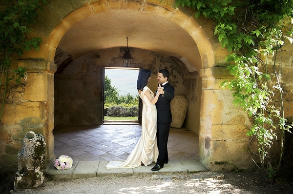 Bride and groom under arch at Château de Bagnols in France